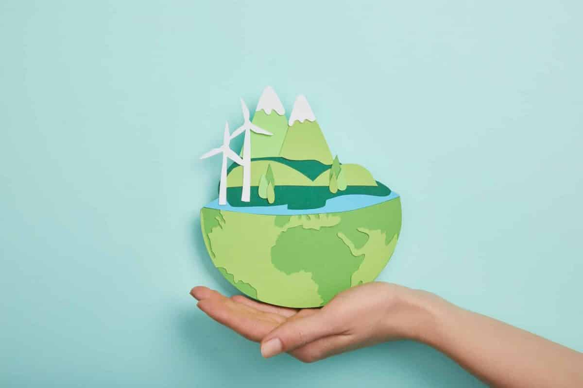 top view of woman holding paper cut planet with renewable energy sources on turquoise background,